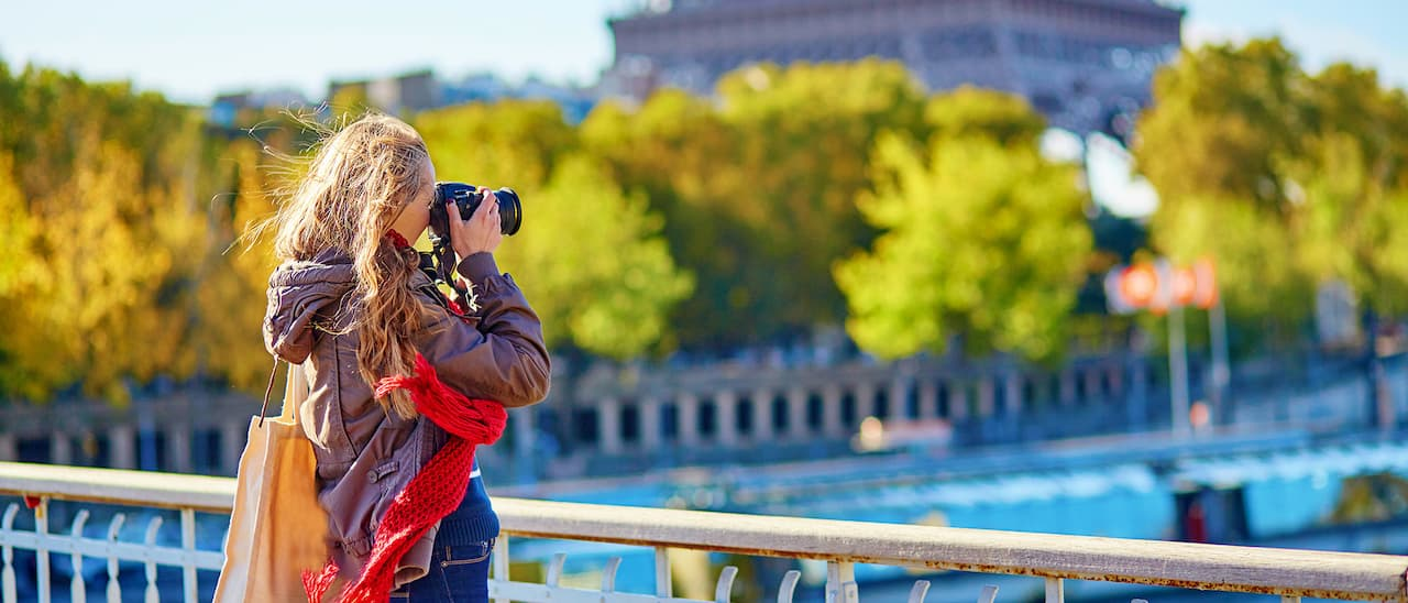 A woman with an SLR camera captures an image of the Eiffel Tower in the distance