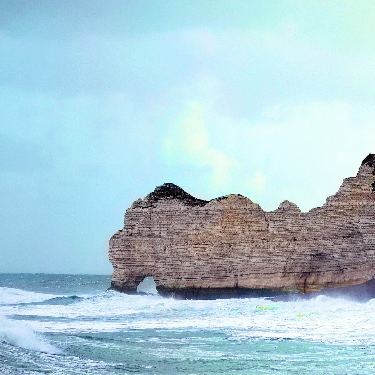 The Cliffs of Étretat with the natural arch jutting out into the Atlantic Ocean