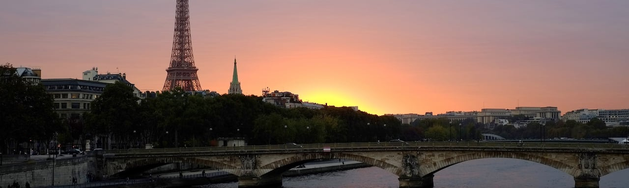 A bridge over the Seine River and the Eiffel Tower at sunset