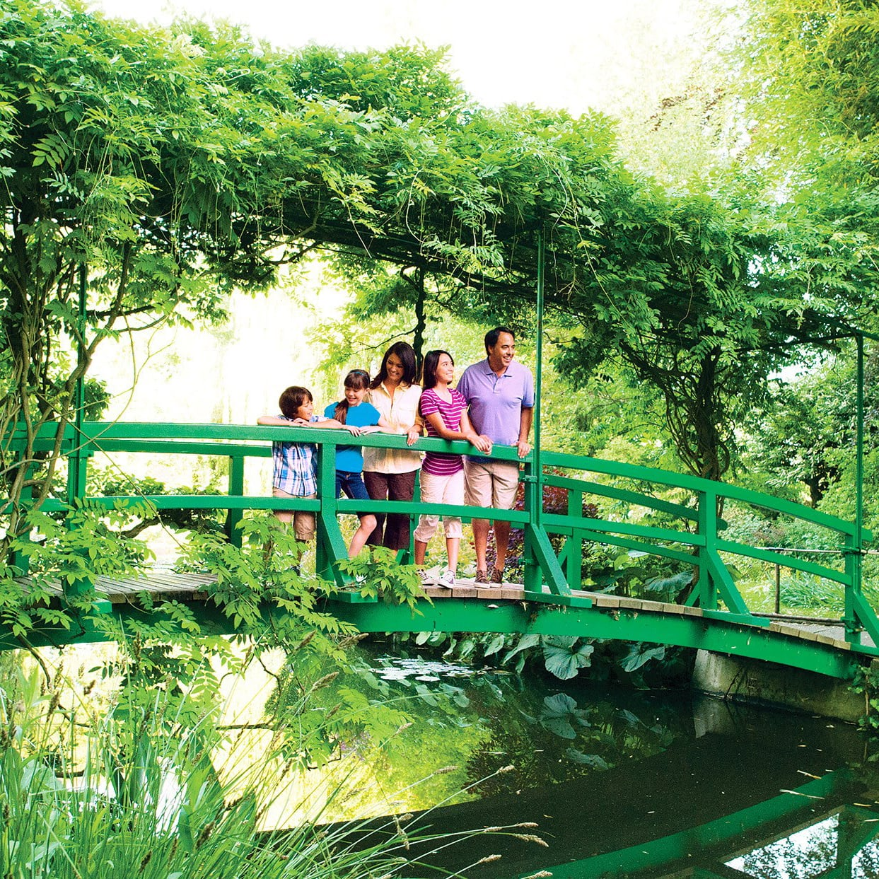 A family of 5 stands on a bridge at the house of Claude Monet in Giverny, France