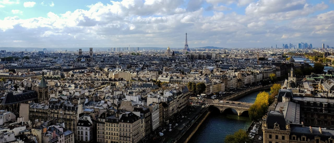 The Seine River flows through the city of Paris, France with the Eiffel Tower in the distance