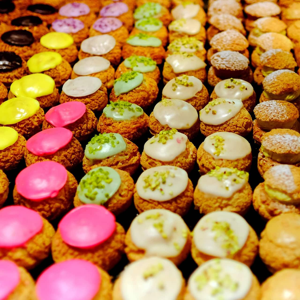 Rows of colorful French éclair pastries