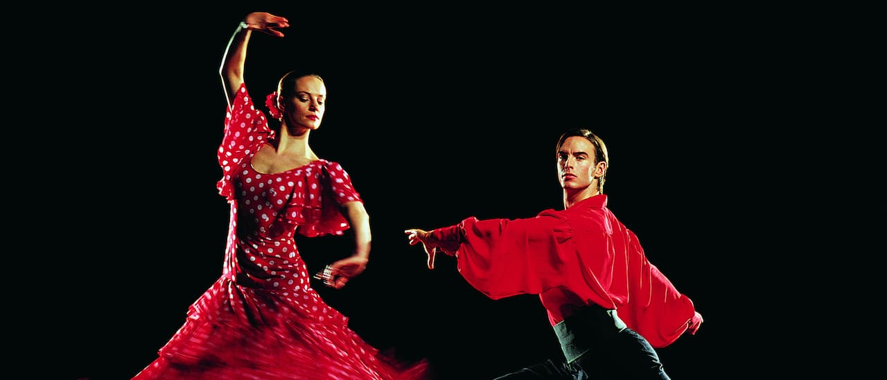 Costumed male and female flamenco dancers pose in dance positions