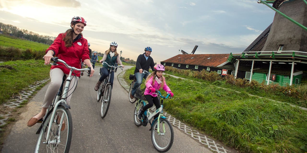 An Adventure Guide riding bikes with a socially distant group on a path with windmills