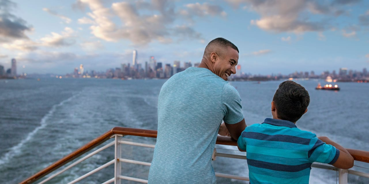 A father and his son look at a distant city from the railing of a ship sailing over a body of water
