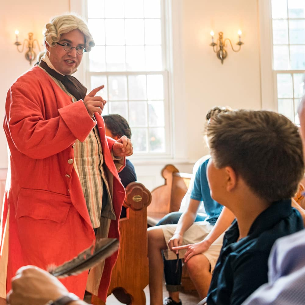 A man in period costume addresses a group of Adventurers at the Boston Tea Party Museum