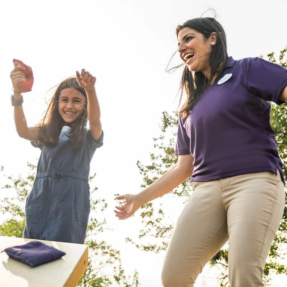 Two girls and an Adventure Guide play a game of cornhole