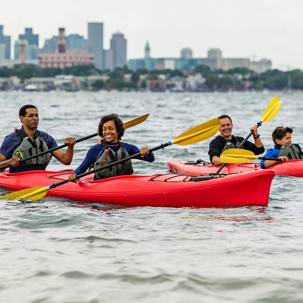A group of Adventurers in 3 2-person kyaks row in the water with the Boston skyline in the background