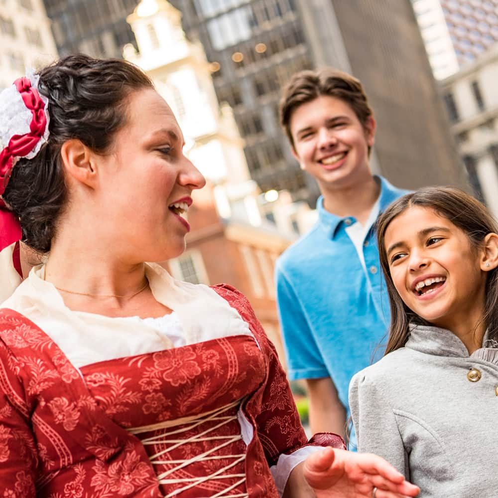 A woman in period costume talks with a young girl and an Adventure Guide