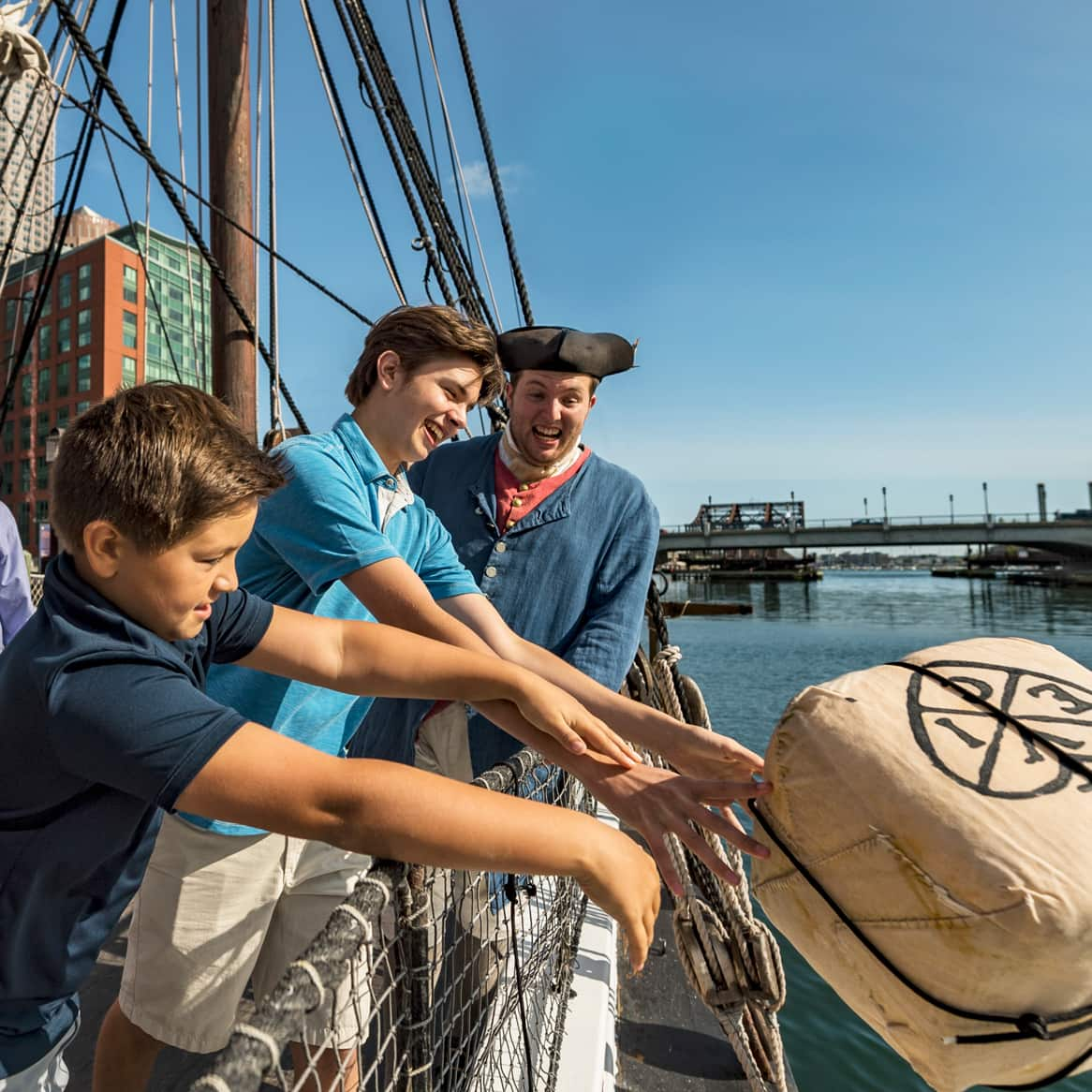 People look on as a young boy throws a crate of tea over a boat railing