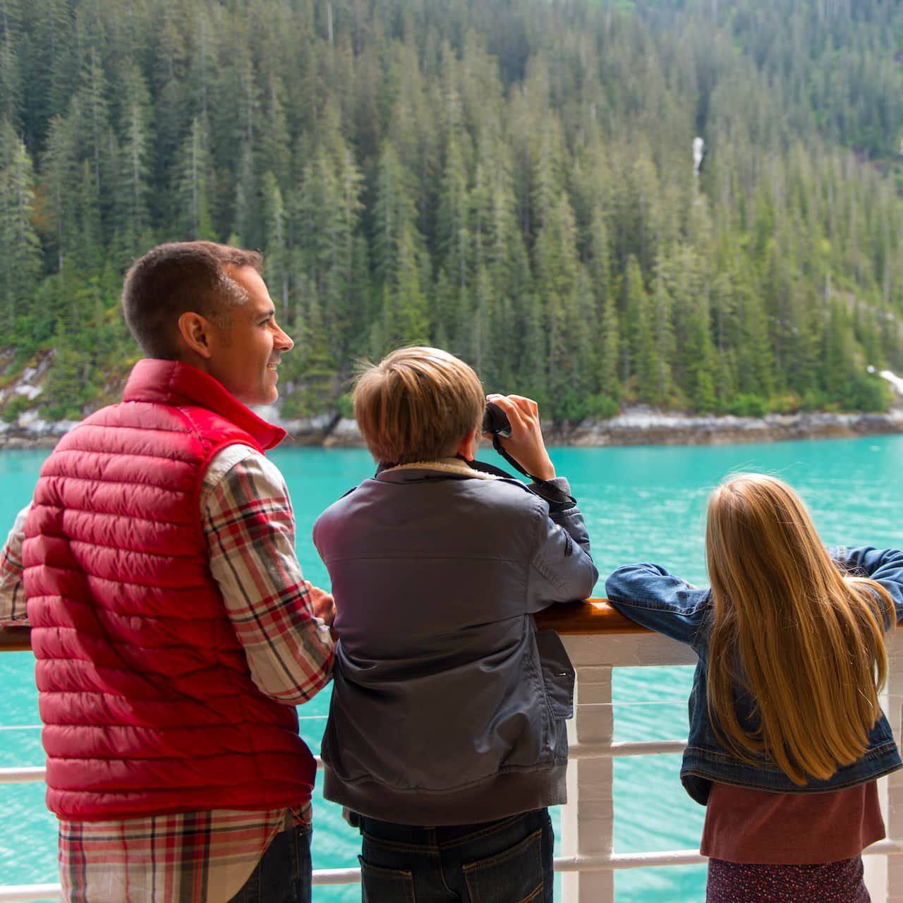 A family of 4 looks at the tree-covered Alaskan wilderness from over a ship's railing