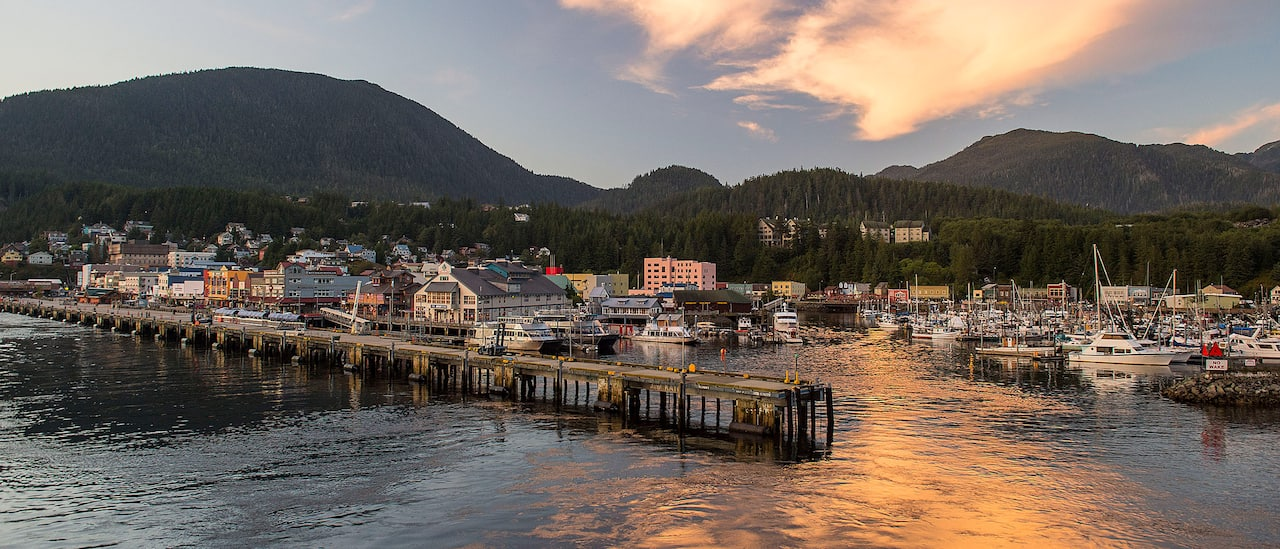 A pier juts out into the water near a small Alaskan seafront town