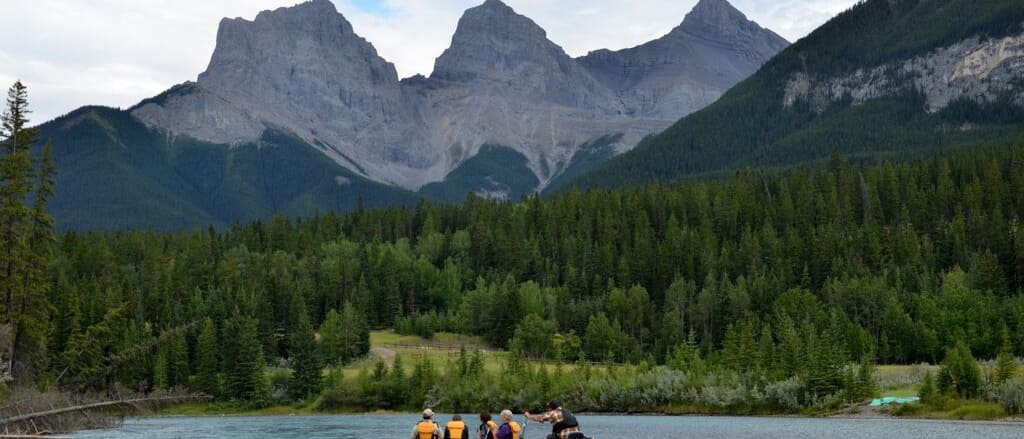A group of people raft on a river near a pine tree-filled riverbank at the base of a mountain