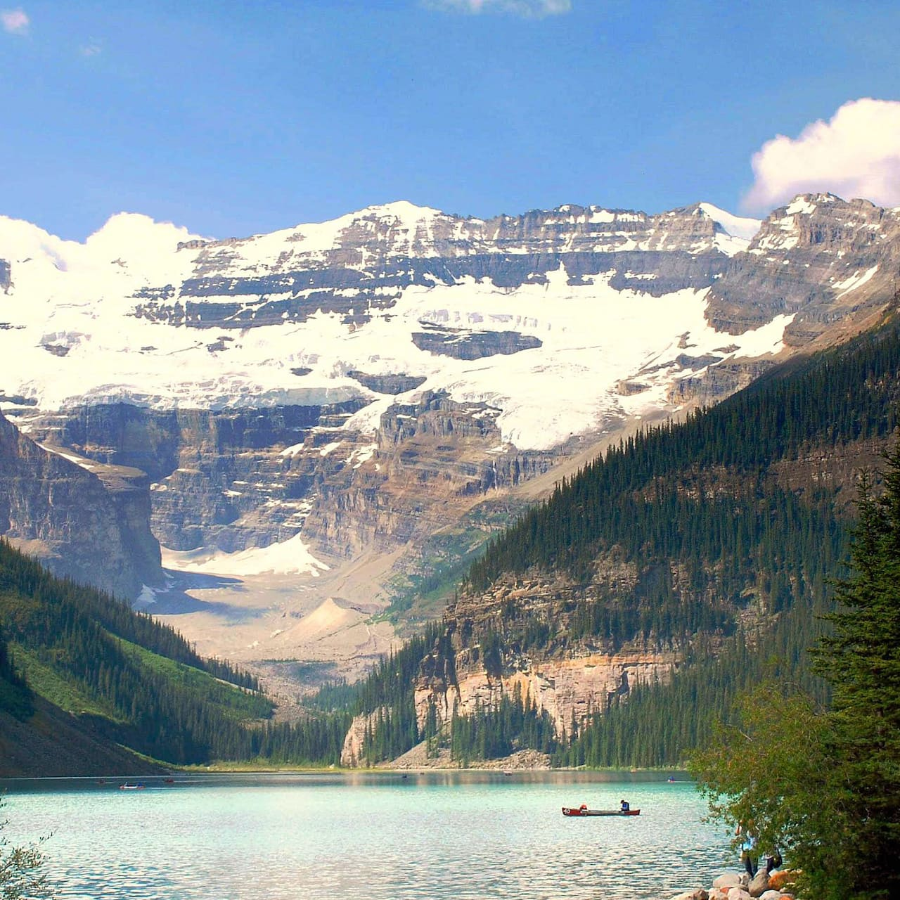 A lone canoe sits on Lake Louise, surrounded by snow-capped mountains