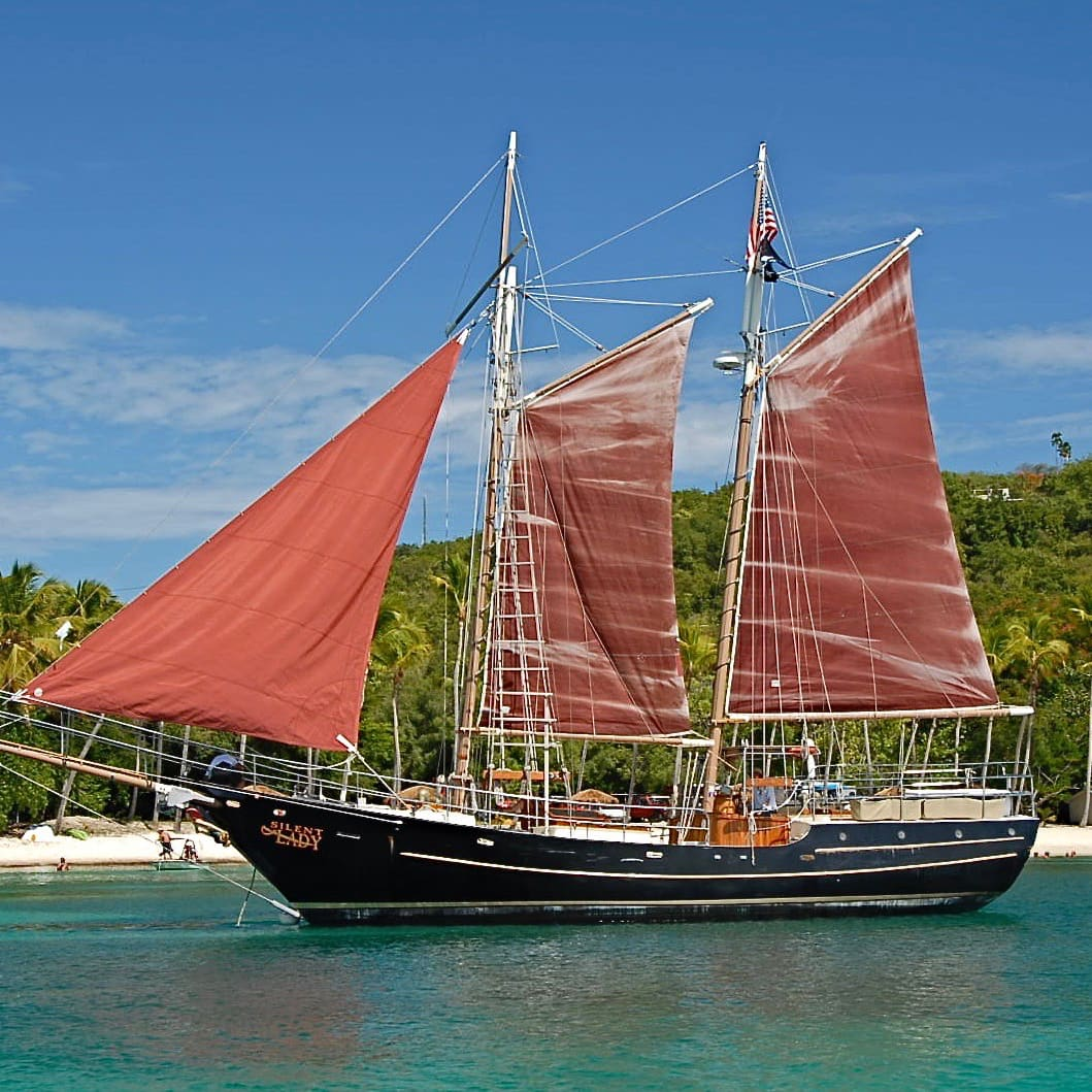 A 2-masted ship flying 3 sails is anchored in the water just off the shore of a tropical beach