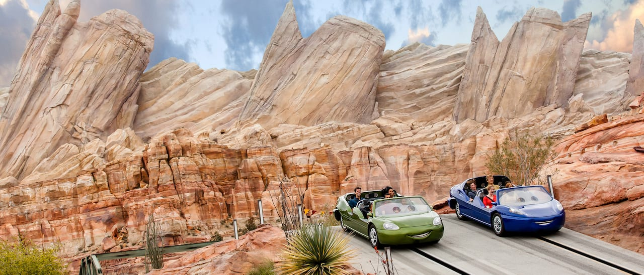 Two cars filled with families race in the rock canyon of Cars Land at Disney California Adventure Park