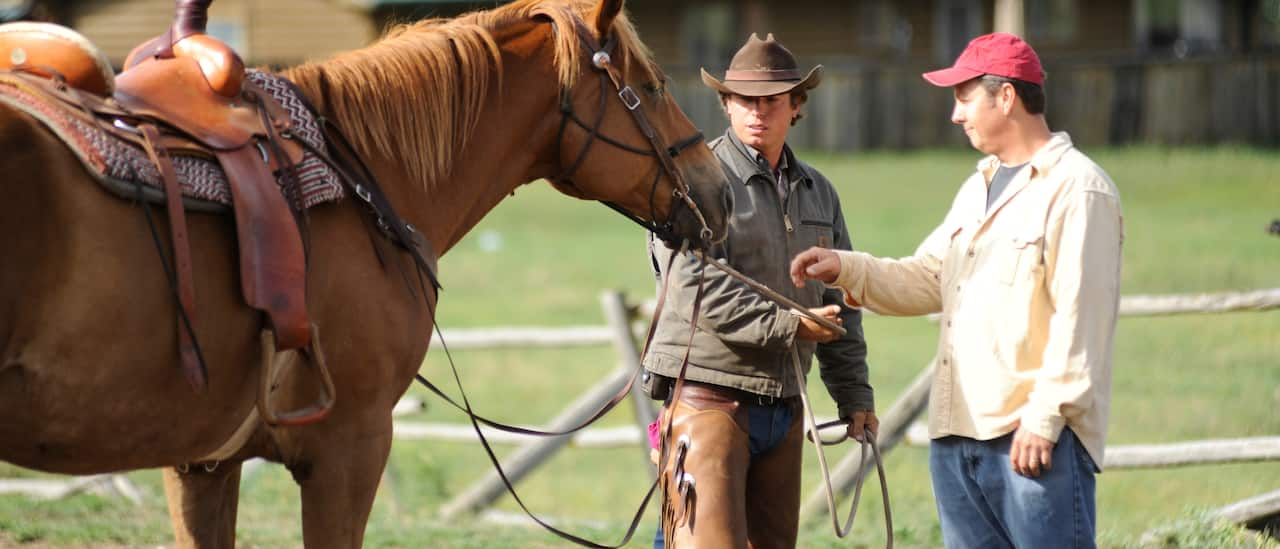 A cowboy hands a Guest the reins of a horse