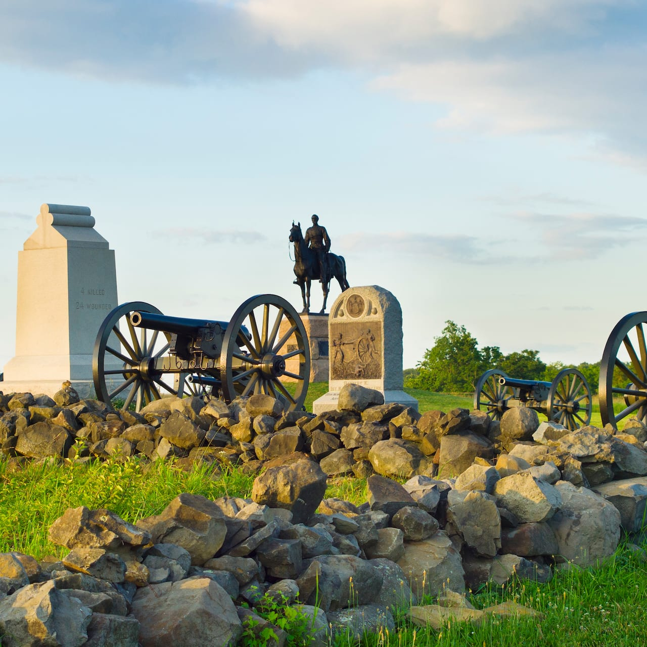 Tombstones, 3 cannons and a statue of a man on a horse at Gettysburg National Military Park