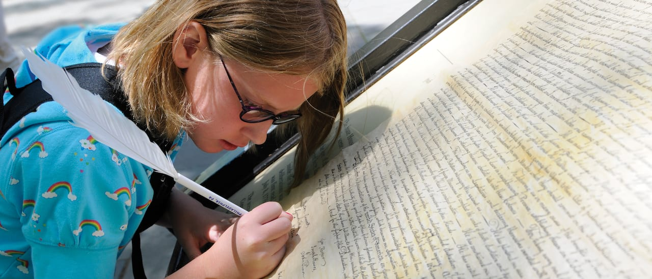 A girl signs a huge facsimile of the Declaration of Independence