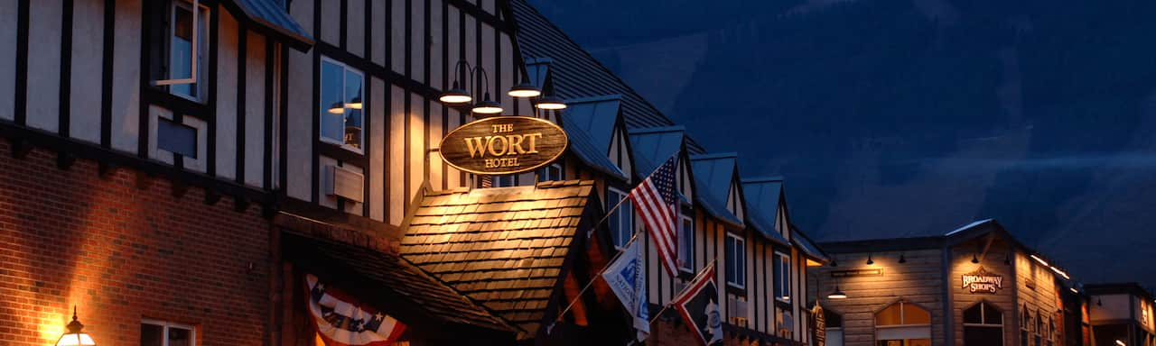 At night, a lit sign above the entrance to a building made of wood and brick reads 'The Wort Hotel'