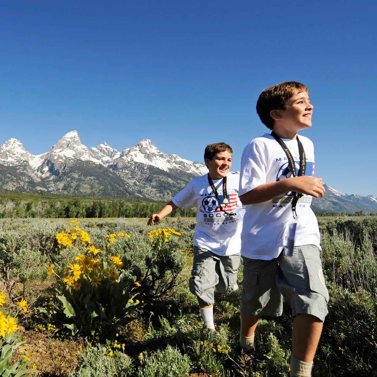 2 boys run through a field near snow dusted mountains