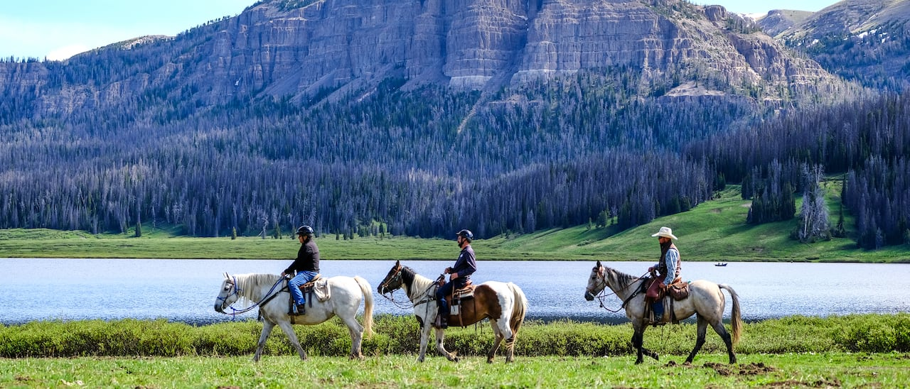 Three people on horseback ride across a river from a mountain with a tree-lined base