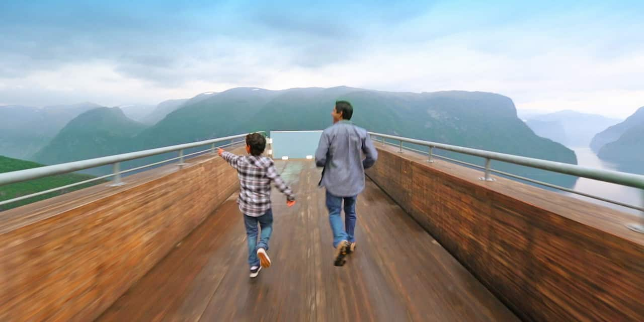 An excited father and son run down a wood-paneled skyway to view mountains and a winding river