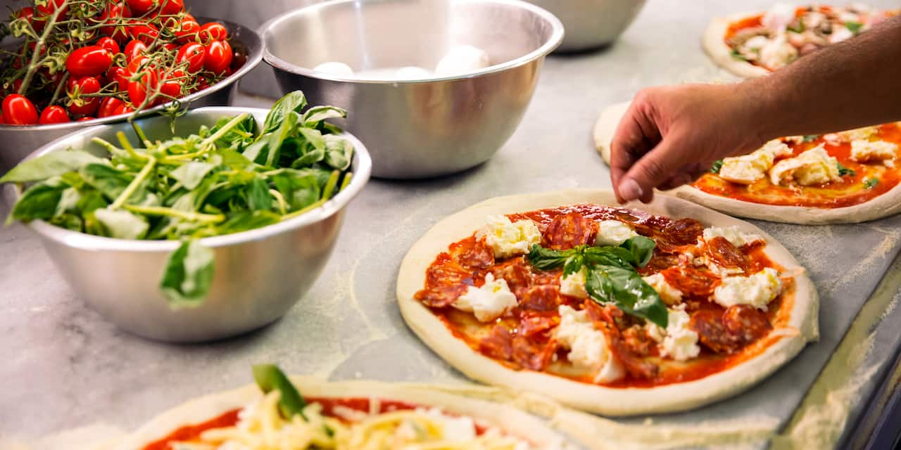 A hand sprinkles herbs on one of several pizzas lined up on a counter near metal mixing bowls filled with ingredients