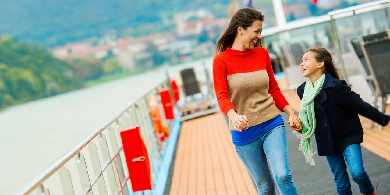 A mother and daughter laugh with one another as they ride a ferry with green hills in the distance