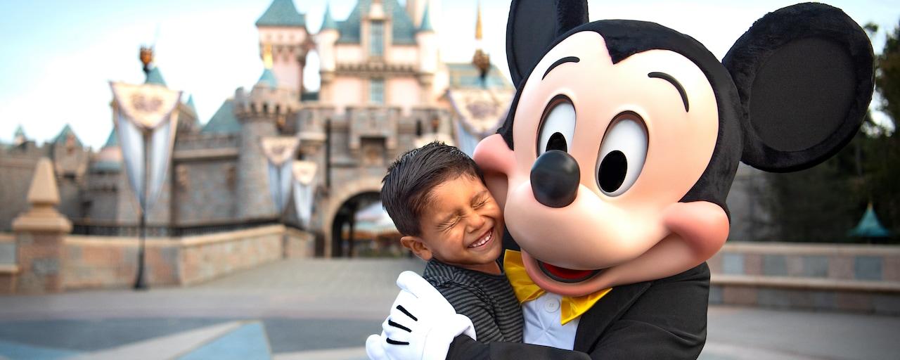 Mickey Mouse comparte un abrazo con un pequeño feliz invitado frente al Castillo de la Bella Durmiente