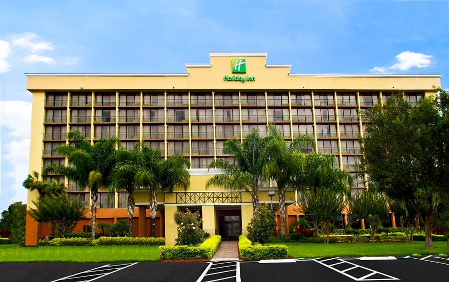 Exterior of the Holiday Inn with hotel signage and a manicured lawn with palm trees, hedges and a brick pathway