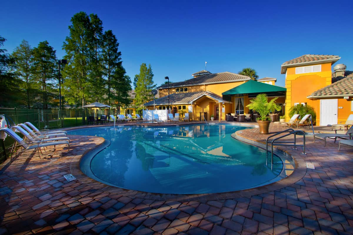 A gated outdoor pool area featuring lounge chairs and more