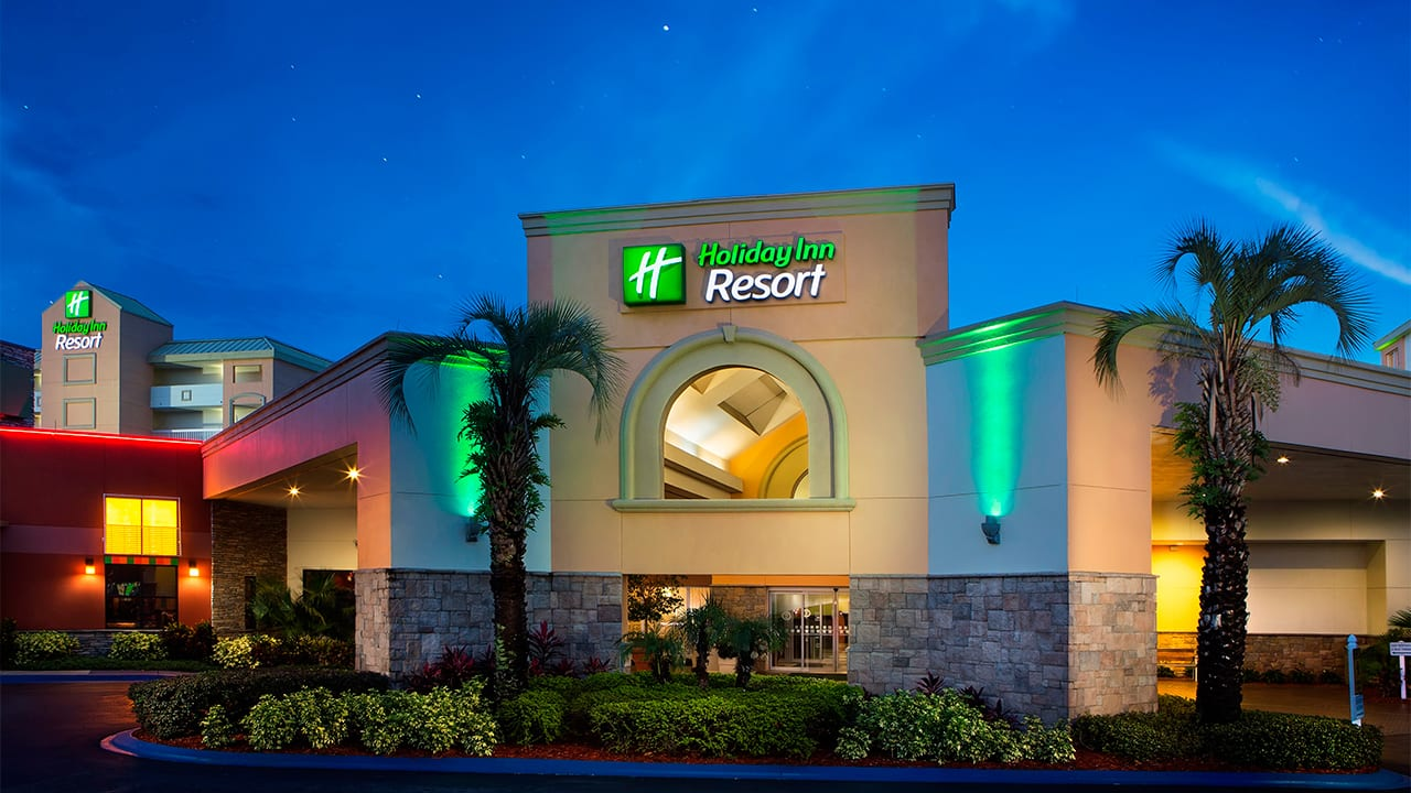 Exterior entrance to Holiday Inn Resort in Orlando framed by palm trees and lit up at night