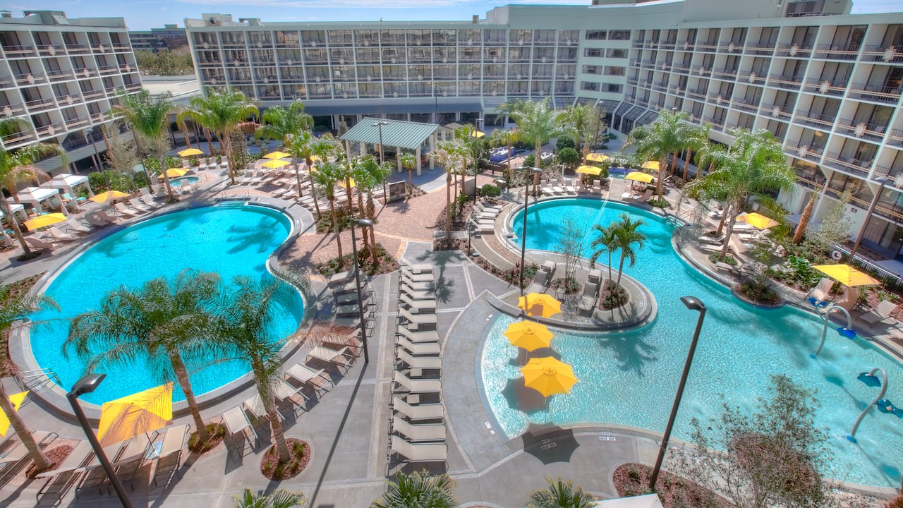 Two pools on a large patio with palm trees, chaise lounges, umbrella tables and a bar