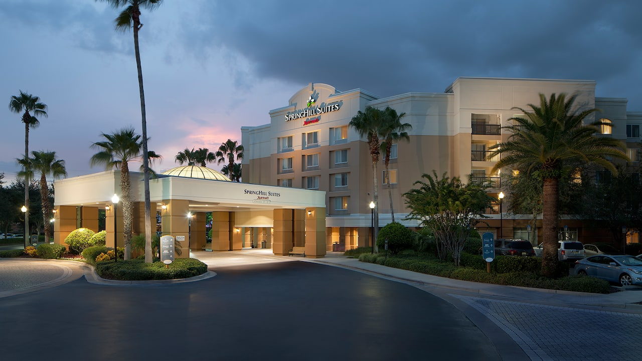 The exterior of Springhill Suites Marriott hotel, with a brightly lit driveway and palm trees
