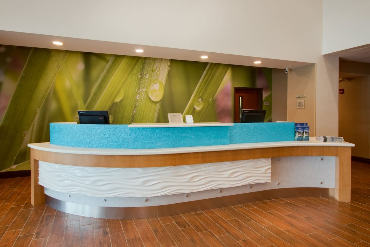 Curved hotel lobby desk with wood floors and wet blades of grass wallpaper