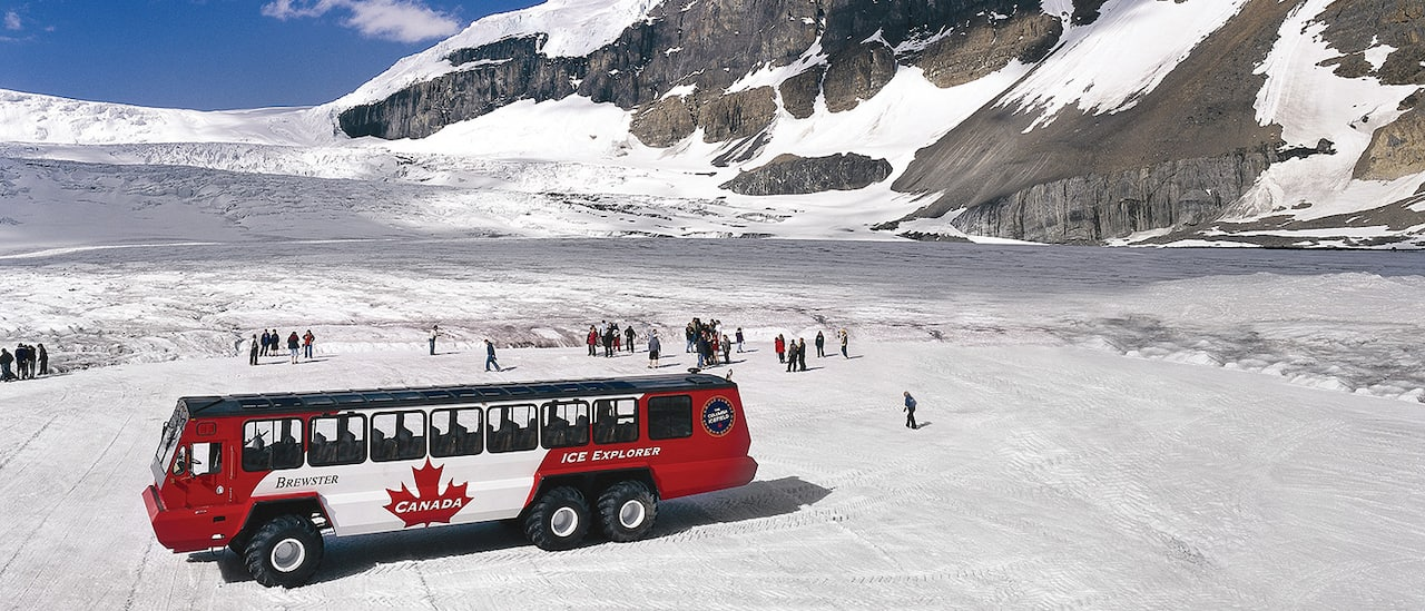 An ice expedition vehicle is parked by its passengers on a mountainside ice field