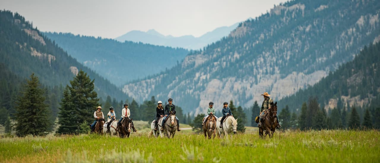 A group of people ride horses on the grassy plain of a mountain valley