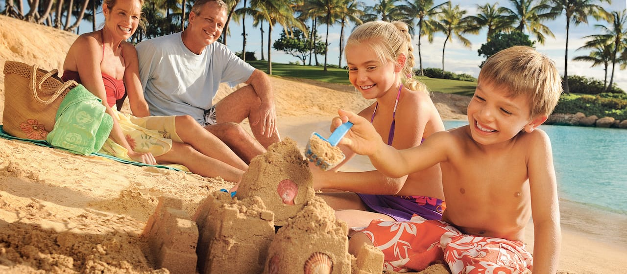 Two adults look on as their smiling kids build a sand castle on the beach