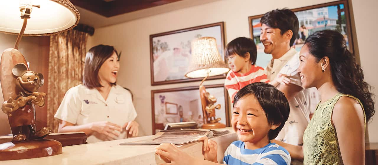 Two parents and their two young boys talk with a Disney Vacation Club Guide who is standing behind a counter