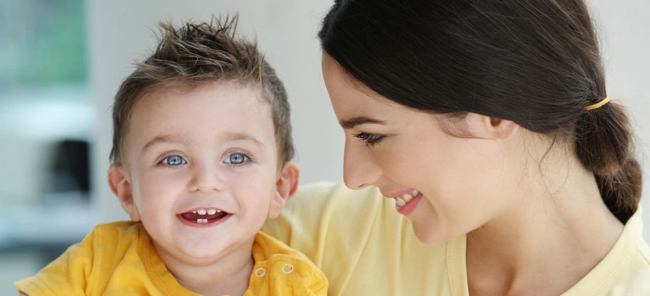 A female caregiver smiles at a young boy