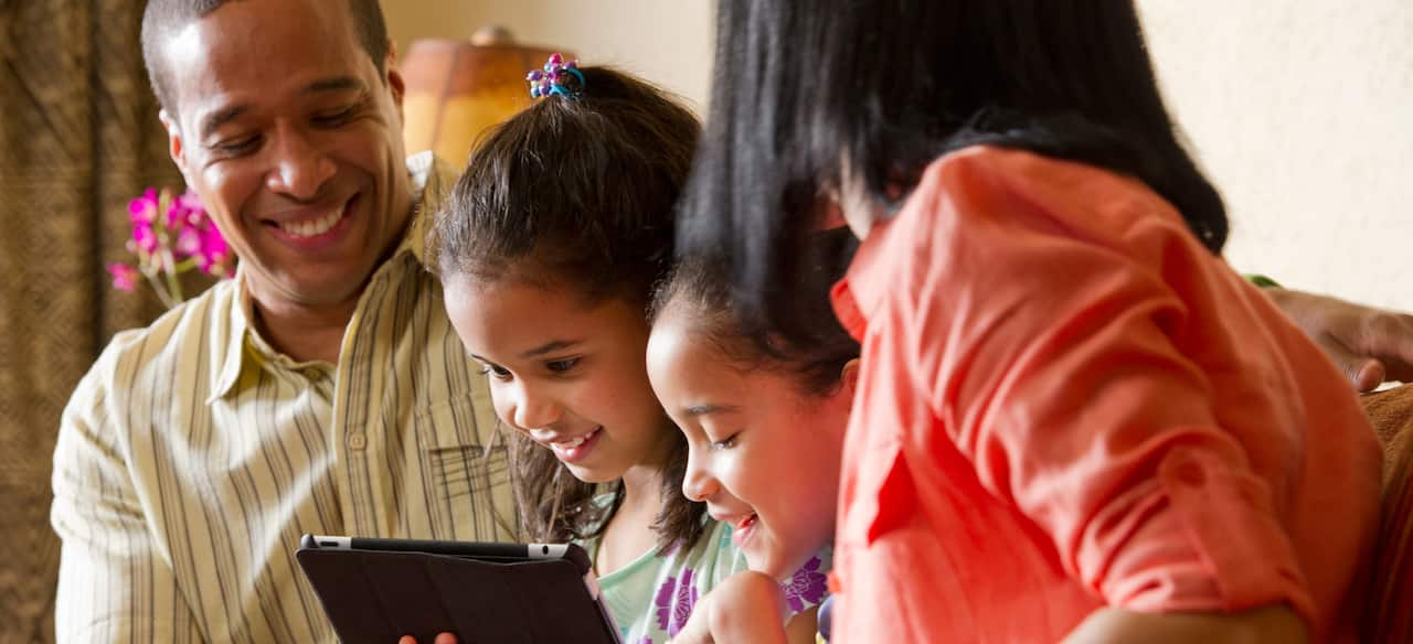 A girl interacts with a mobile tablet as her sister and parents look on
