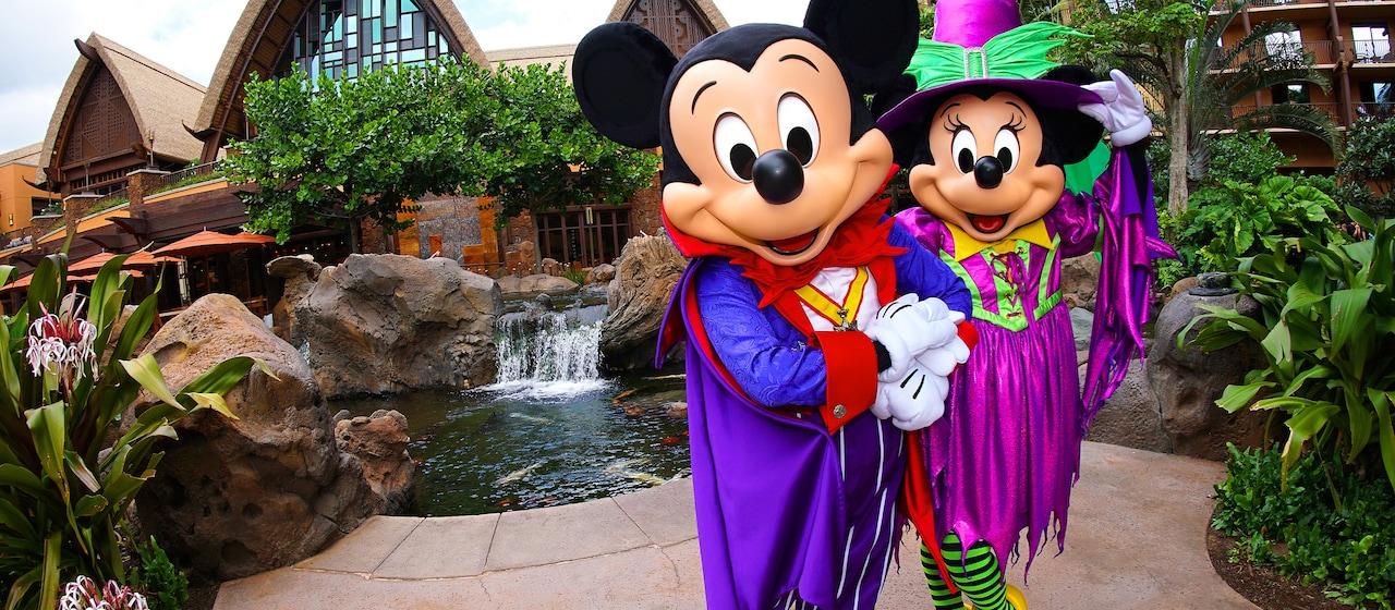 庭園でとんがり帽子と魔女の恰好に身を包んでポーズを決めるミニーマウスと、傍らでドラキュラのケープ姿でポーズを決めるミッキー。