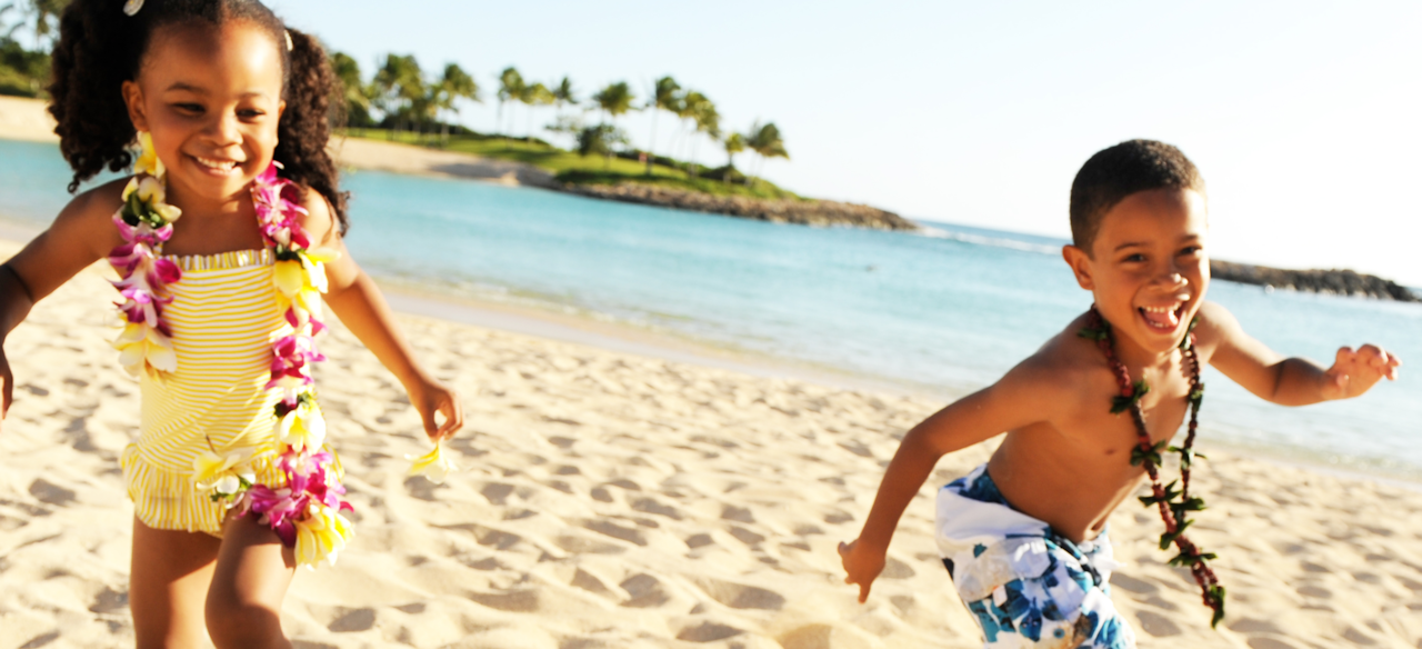 A small girl and boy wearing swimwear and Hawaiian necklaces frolic on a tropical beach