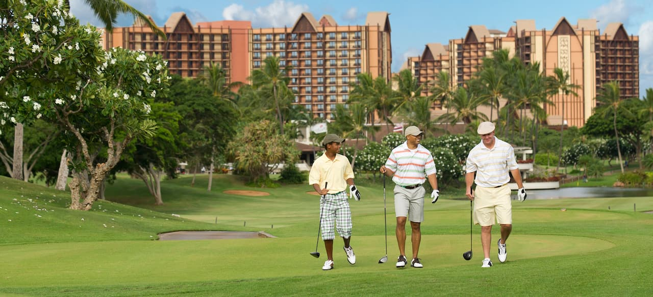 Three men in golf attire walk across the green, each carrying a golf club