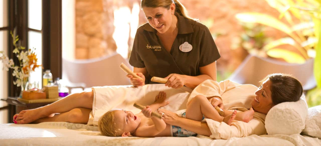 A smiling mother and baby lie on a massage table while a spa practitioner with massage sticks looks on.