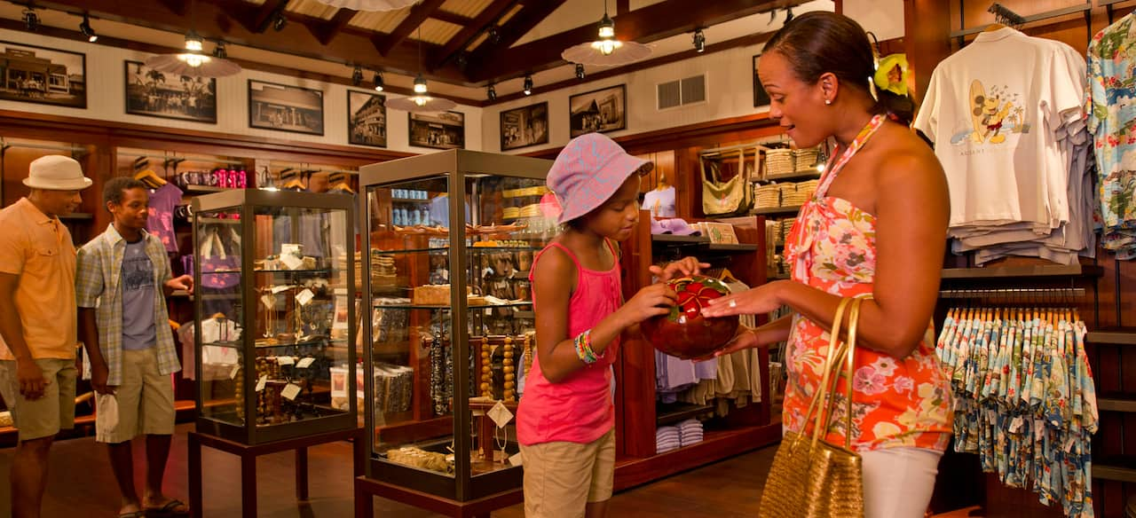 A mother and daughter examine a ceramic vessel while a father and son eye a jewelry display case