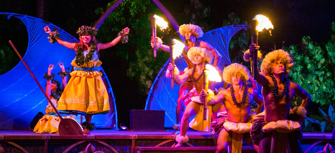 Four male performers solemnly hold lit torches aloft while 2 female dancers raise their hands skyward