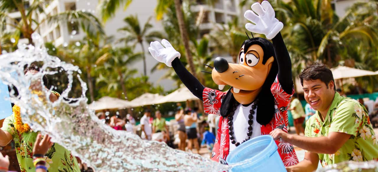 A Cast Member throws a bucket of water while Goofy, dressed in Hawaiian garb, waves his hands in the air