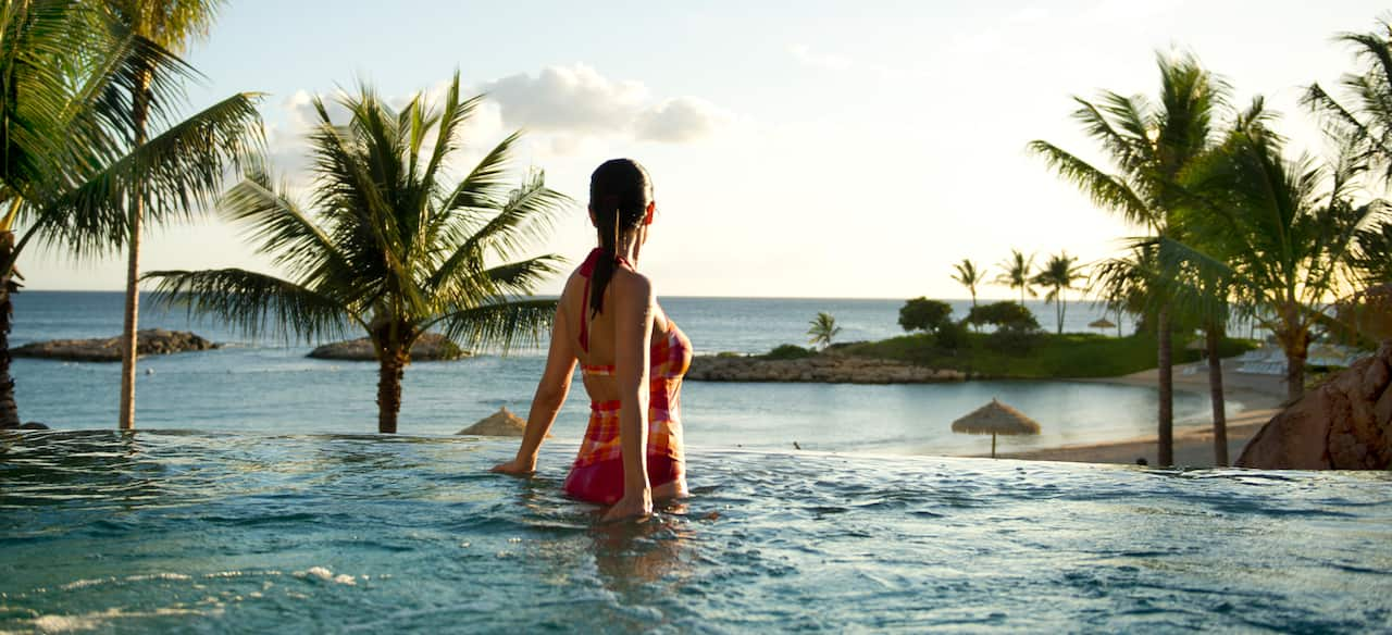 A bathing suit-clad female guest enjoys a whirlpool spa while gazing at the clouds above the ocean